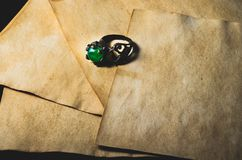 Ring with shinny green gem and ancient parchment royalty free stock photos