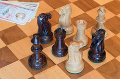 Ring at stake. A chess game in the process with money and engagement ring at stake Royalty Free Stock Image