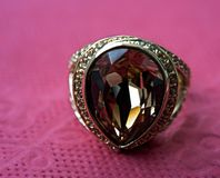 A ring with a stone. Beautiful ring with a stone lying on the table. Transparent stone faces are in the sun Stock Image