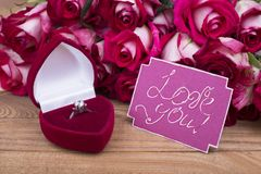 Ring with stone and flowers. `Love you` and box with ring. Bright proposal of the hand and heart stock images