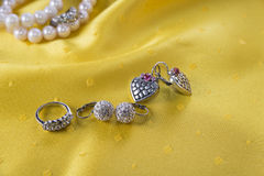 Ring and two pairs of earings on the yellow stock images