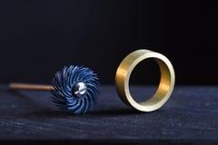 Ring van goud en een oppoetsend hulpmiddel op de werkbank van een goldsm royalty-vrije stock afbeelding