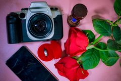 Ringa i röd ask, härlig röd ros, telefon, kamera och timglas Arkivfoton