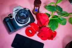 Ringa i röd ask, härlig röd ros, telefon, kamera och timglas Arkivbild
