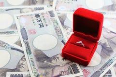 Ringa i röd ask med yensedlar i bakgrund royaltyfria foton