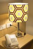 Ringa på en tabell nära till en lampa Royaltyfria Bilder