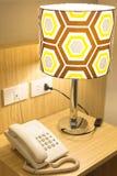 Ringa på en tabell nära till en lampa arkivfoto