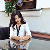 Ringande nummer för härlig flicka på en utomhus- mobiltelefon - Arkivfoto