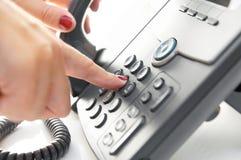 Ringande telefonnummer för kvinnligt finger arkivbilder