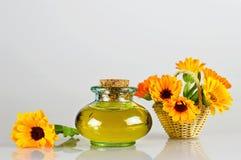 Ringblommaolja och blommor i korgen Arkivfoton