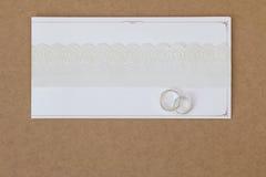 2 Ringe auf einer Hochzeitseinladungskarte mit weißem Spitzenpapier ribbo Lizenzfreies Stockbild