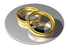Ringe der goldenen Hochzeit auf einer reflektierenden Platte Stockbild