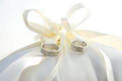 Ringe der goldenen Hochzeit, die auf Ringkissen legen Lizenzfreies Stockfoto