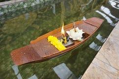 Ringelblume und weißer Lotos mit Kerze im mini hölzernen Boot auf klarem Wasser, Gebrauch der thailändischen Leute für wehren das Stockbild
