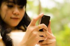 Ringer den leka cellen för den asiatiska flickan Royaltyfri Bild