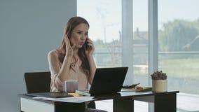 Ringer den talande mobilen f?r aff?rskvinna Frilans- dam som arbetar på bärbar datordatoren stock video