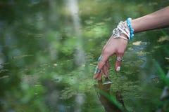 Ringer rörande vatten för kvinnahanden med bohostil och armbanden royaltyfria bilder