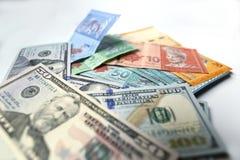 Ringgit malaio e dólar de Estados Unidos em um fundo branco Imagens de Stock