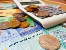 RinggitMalaysia sedlar och mynt med räknemaskinen royaltyfria bilder
