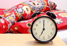 Ringing alarm clock and empty bed in background Stock Image
