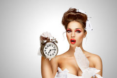 Ringing clock. Sexy pinup bride in a vintage wedding corset holding a retro alarm clock on grey background Royalty Free Stock Photos