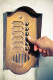 Ringing a door bell. A visitor pushing a brass, antique doorbell stock photo