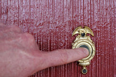 Ringing Doorbell. Finger of a man's hand ringing a gold and black door bell on a brick red house Stock Photo