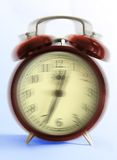 Ringing old style alarm clock (movement blur). Ringing retro-styled alarm clock - close up on light blue background (movement blur royalty free stock images