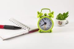 Ringklocka, öppen anteckningsbok och blyertspenna på vit bakgrund Fotografering för Bildbyråer