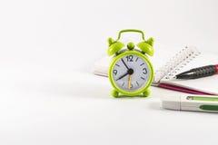 Ringklocka, öppen anteckningsbok, usb-pinne och blyertspenna på vit bakgrund Arkivfoto