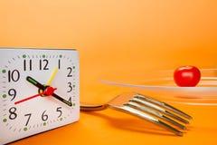 Ringklocka, gaffel och liten körsbärsröd tomat Royaltyfri Bild