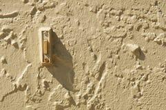 Ringklocka i stuccoed vägg med skugga- och kopieringsutrymme Royaltyfri Fotografi