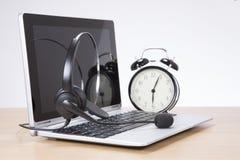 Ringklocka och hörlurar med mikrofon på bärbar datortangentbordet royaltyfri fotografi