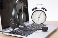 Ringklocka och hörlurar med mikrofon på en bärbar datordator royaltyfria bilder