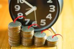 Ringklocka och moment av myntbuntar på den funktionsdugliga tabellen med pilen Royaltyfri Foto