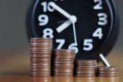 Ringklocka och moment av myntbuntar på den funktionsdugliga tabellen, tid för Royaltyfri Bild