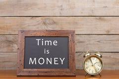 Ringklocka och svart tavla med text & x22; tid är money& x22; Arkivbilder