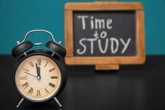 """Ringklocka och svart tavla med uttryck \ """"Tid att studera \"""" på tabellen Grungebakgrund f?r dina publikationer royaltyfri bild"""
