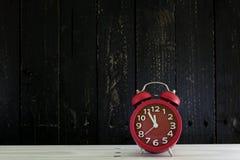 Ringklocka på den vita wood tabellen, fem minuter till `-cloc för nolla tolv Royaltyfria Foton