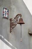 Ringklocka retro gammal stil Med kedjan Hus nummer 9 i solsken Royaltyfri Foto