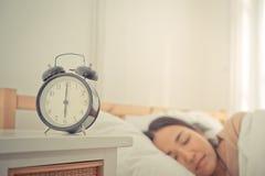 Ringklocka som fortfarande räknar till sex nolla klockan med kvinnan i säng Arkivbilder