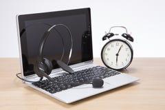 Ringklocka tillsammans med en bärbar dator och en hörlurar med mikrofon royaltyfria bilder