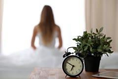 Ringklockaanseendet på nattduksbordet har redan ringt otta för att vakna upp kvinna i sängsammanträde i bakgrund royaltyfri bild