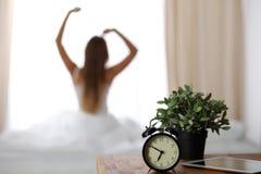 Ringklockaanseendet på nattduksbordet har redan ringt otta för att vakna upp kvinna sträcker i säng i bakgrund arkivbild
