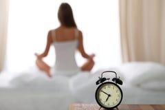 Ringklockaanseendet på nattduksbordet har redan ringt otta för att vakna upp Kvinnan gör yoga i säng i bakgrund royaltyfri fotografi