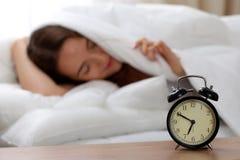 Ringklockaanseendet på nattduksbordet har redan ringt otta för att vakna upp kvinnan i säng som sover i bakgrund fotografering för bildbyråer