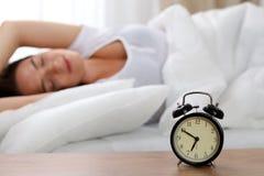 Ringklockaanseendet på nattduksbordet har redan ringt otta för att vakna upp kvinnan i säng som sover i bakgrund arkivfoton