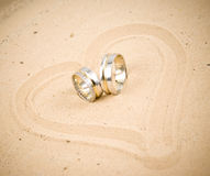 Rings. Wedding rings on sand with heart shape Stock Photography