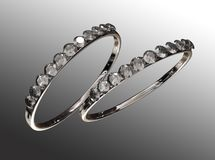 Rings. Two rings with diamonds against a grey background stock illustration