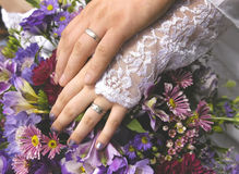 Rings. Wedding rings, hands and bouquet Royalty Free Stock Image